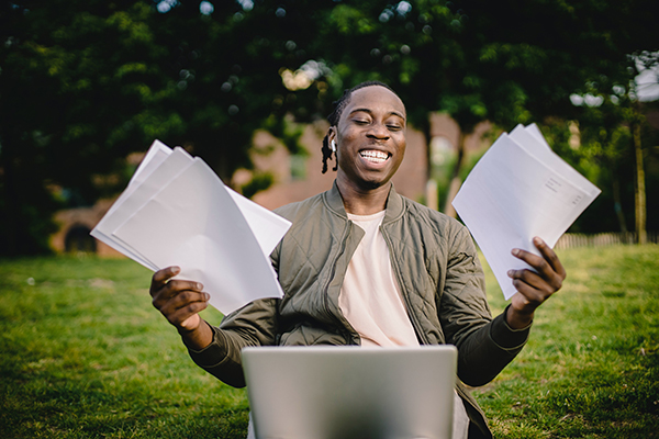 Man sitting with laptop holding papers
