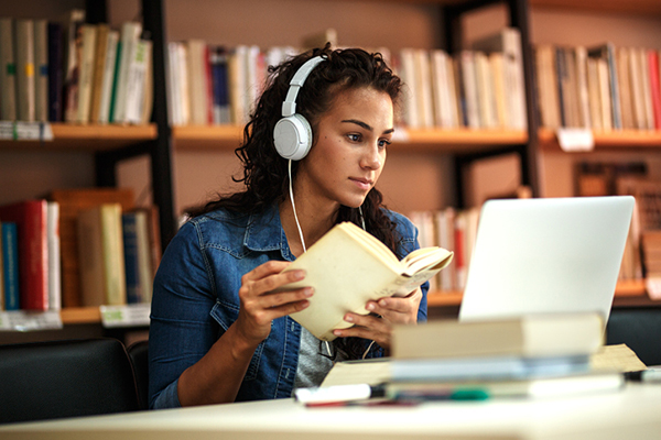Woman wearing headphones reading a book